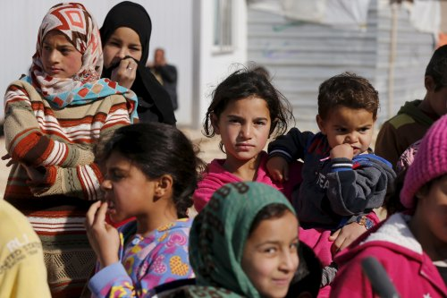 Syrian refugees watch as Britain's Foreign Secretary Philip Hammond visits Al Zaatari refugee camp in Mafraq, Jordan